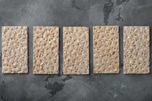 Conjunto de pilha de pão crocante integral com sementes de girassol, chia e gergelim, na mesa de pedra cinza, vista de cima plana lay