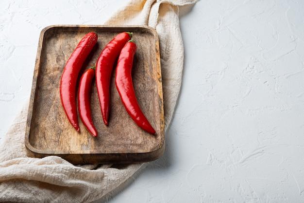 Conjunto de pimenta vermelha crua, em mesa texturizada branca