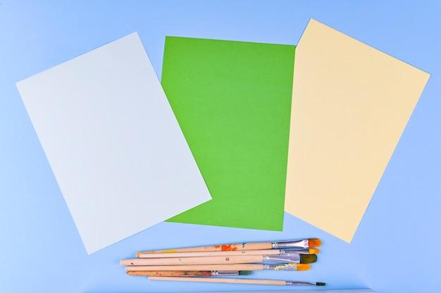 Conjunto de pincéis de artista plana com dicas desenhadas sobre um fundo azul branco e latas de tinta