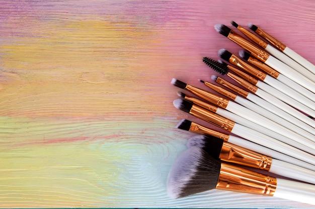 Conjunto de pincéis de maquiagem em um arco-íris de madeira. espaço livre para texto.