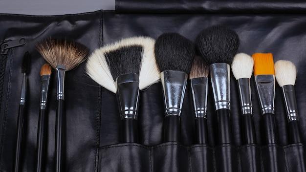 Conjunto de pincéis de maquiagem em um estojo de couro, pincéis de sombra para o rosto em fundo cinza.