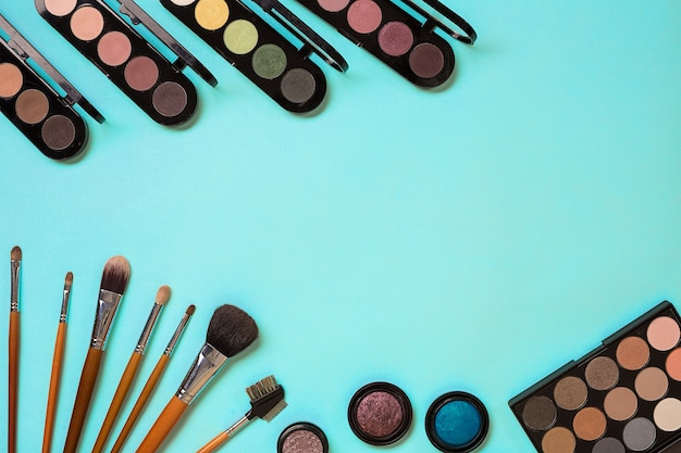 Conjunto de pincéis de maquiagem profissional, cremes e sombras em potes com fundo azul.