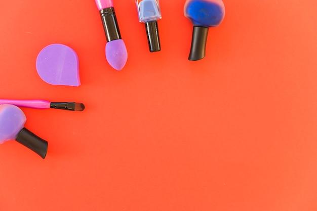 Conjunto de pincéis de maquiagem profissional essenciais; verniz de unhas e esponja sobre fundo vermelho