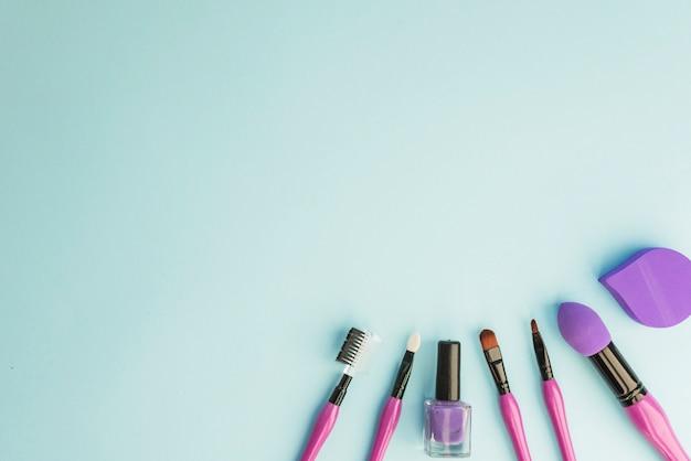 Conjunto de pincéis de maquiagem profissional essenciais; verniz para unhas e esponja sobre fundo colorido