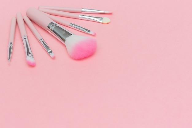 Conjunto de pincéis de maquiagem rosa sobre fundo rosa pastel