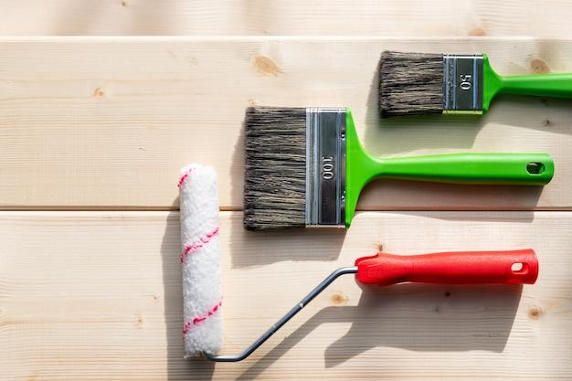 Conjunto de pincéis e rolos para pintura em background de madeira.