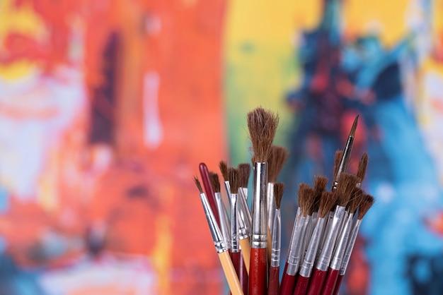 Conjunto de pincéis em uma jarra na frente de uma pintura abstrata