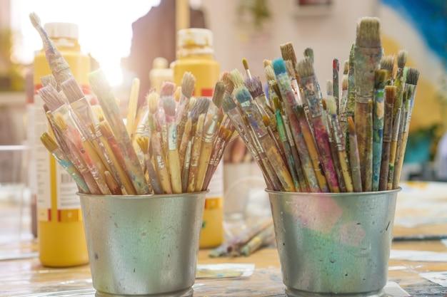 Conjunto de pincéis multicoloridos na xícara. pincéis e tintas para desenho. interior da escola de arte para desenhar crianças. conceito de criatividade e pessoas.