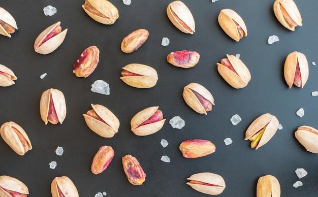 Conjunto de pistache único inshell e pistache pelado com grandes cristais de sal em fundo preto