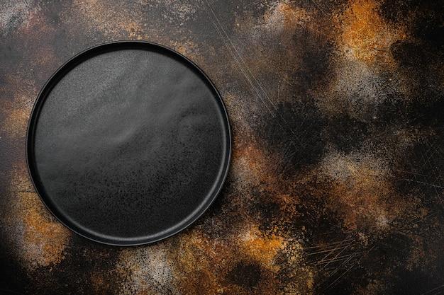 Conjunto de placa preta vazia de cerâmica, no antigo fundo escuro de mesa rústica
