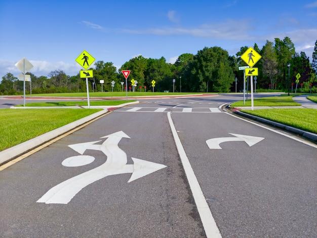 Conjunto de placas de rua e marcações rodoviárias na entrada de um anel