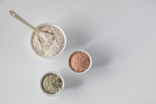 Conjunto de pós de lama de argila cosmética diferente na superfície branca