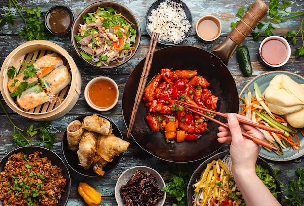 Conjunto de pratos chineses variados na mesa: frango agridoce na frigideira wok, dim sum no vaporizador de bambu, rolinhos primavera, macarrão, salada, arroz, pãezinhos no vapor, molhos. jantar estilo asiático ou buffet, vista de cima