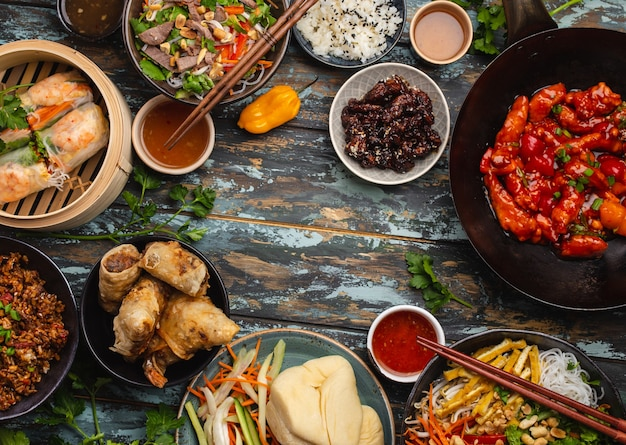 Conjunto de pratos chineses variados na mesa: frango agridoce na frigideira wok, dim sum, rolinhos primavera, macarrão, salada, arroz, pãezinhos no vapor. jantar estilo asiático ou buffet com vista de cima e espaço para texto