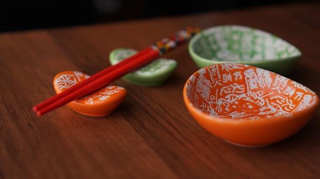 Conjunto de pratos de cerâmica para sushi e sushi vermelho em palitos em fundo de madeira