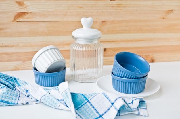 Conjunto de pratos de cerâmica: pratos pequenos e jarra de vidro na mesa de madeira