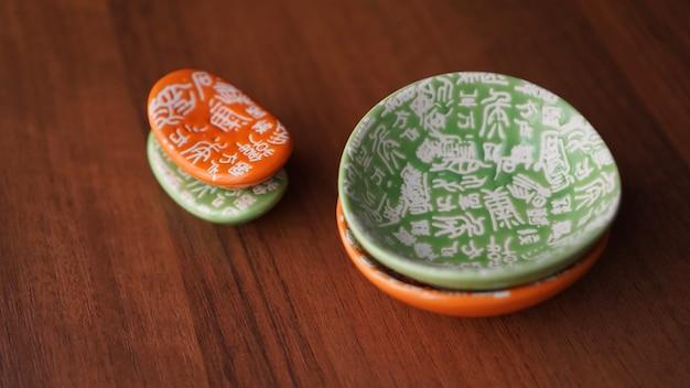 Conjunto de pratos de cerâmica verdes e laranja vazios e carrinhos para sushi em fundo de madeira