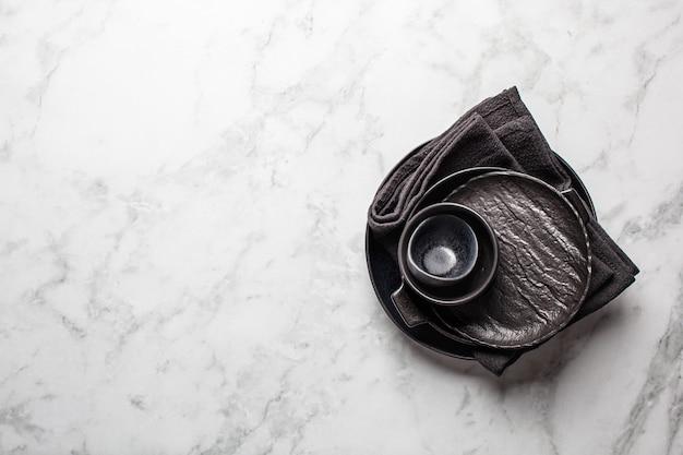 Conjunto de pratos vazios pretos sobre fundo de mármore branco, copie o espaço. cozinhar fundo.