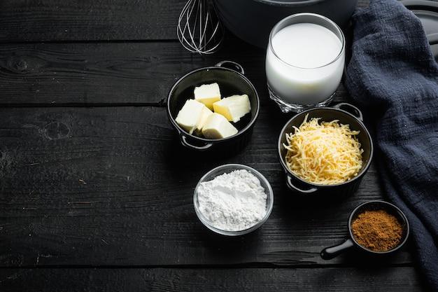 Conjunto de preparação do molho branco de queijo bechamel, na mesa de madeira preta