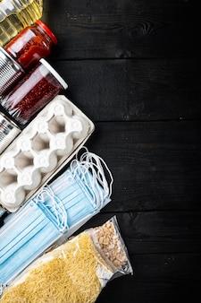 Conjunto de produtos alimentares. abastecimento de alimentos. conceito de doação, coronavírus e quarentena, vista superior com espaço de cópia, na mesa de madeira preta
