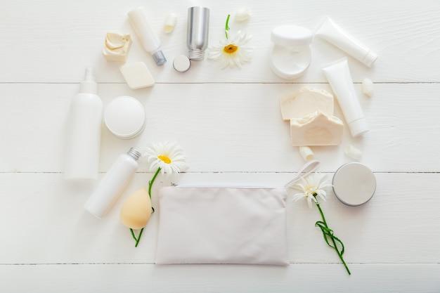 Conjunto de produtos de banho naturais para a pele em embalagem branca na mesa de madeira. cosméticos de spa para beleza, saúde em casa. bolsa de cosméticos, produtos de higiene, flores, sabonete, creme hidratante. espaço de cópia de quadro de maquete.