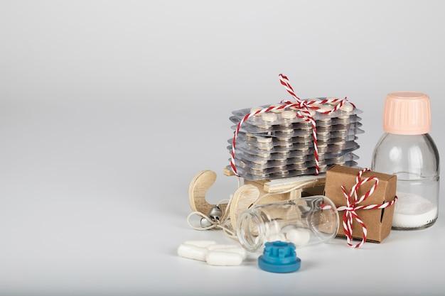 Conjunto de produtos farmacêuticos no trenó de madeira decorativo. plano de fundo cinza.