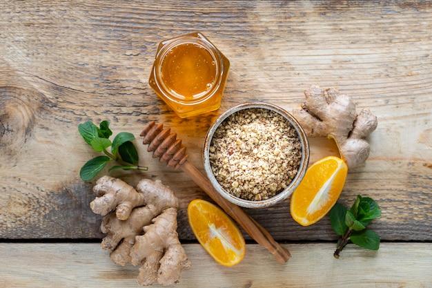 Conjunto de produtos para impulsionar o sistema imunológico. mel, limão, nozes, gengibre para aumentar a imunidade. vista do topo. copie o espaço