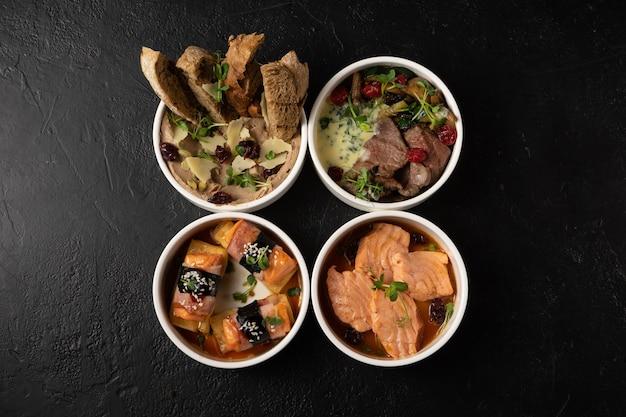 Conjunto de quatro petiscos quentes e frios de carnes e peixes. salmão, omelete de bacon japonês, pão com patê de queijo e carne bovina ao molho cremoso.