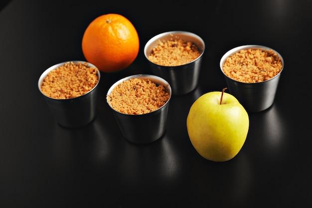 Conjunto de quatro xícaras de aço inoxidável idênticas com sobremesa crumble de maçã, uma laranja e uma maçã amarela atiradas de cima na mesa preta, vista lateral