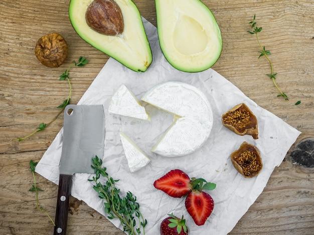 Conjunto de queijo e frutas em uma superfície de madeira