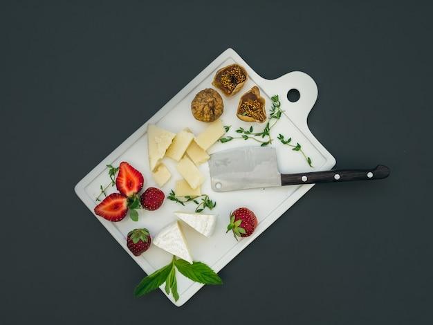 Conjunto de queijo e frutas em uma superfície escura
