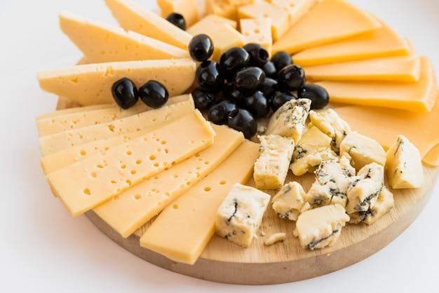 Conjunto de queijo fresco e azeitonas na tábua de cortar madeira
