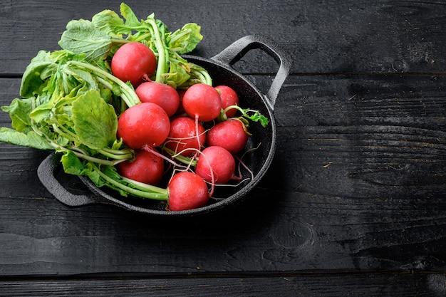 Conjunto de ramo de rabanete vermelho com folhas verdes, na mesa de madeira preta