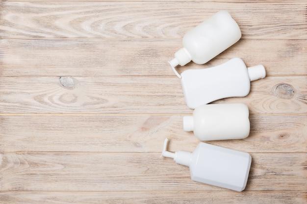 Conjunto de recipientes de cosméticos brancos na madeira
