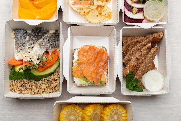 Conjunto de refeições saudáveis para o dia em lancheiras fica em uma mesa branca.