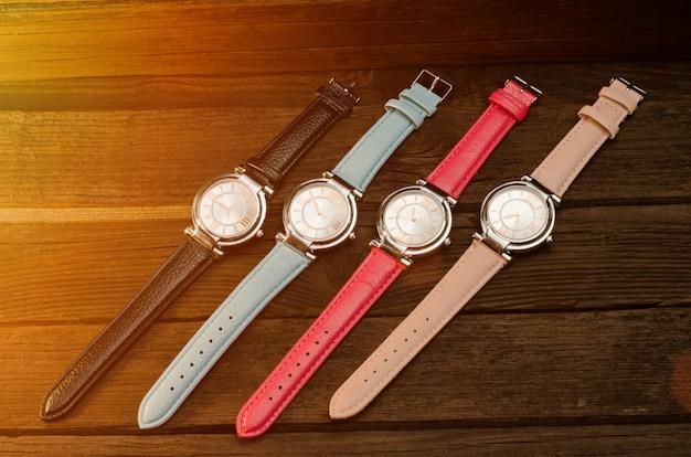 Conjunto de relógios de pulso femininos multicoloridos na mesa de madeira. tonificação