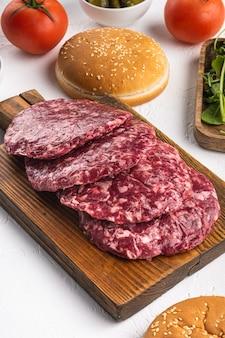 Conjunto de rissóis de carne moída para grelhar e assar, em fundo de pedra branca