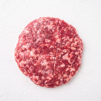 Conjunto de rissóis de carne moída para grelhar e assar, formato quadrado, sobre fundo de pedra branca, vista de cima plano plano