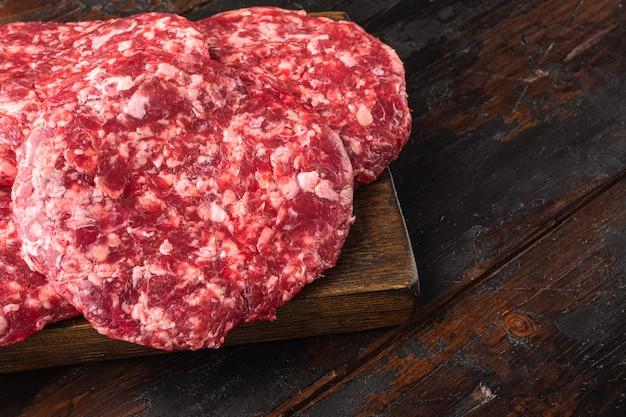 Conjunto de rissóis de carne moída para grelhar e assar, no fundo da velha mesa de madeira escura