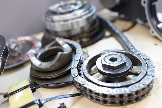 Conjunto de rodas dentadas conectadas com corrente de aço na mesa de serviço esperando para serem verificadas e Foto Premium
