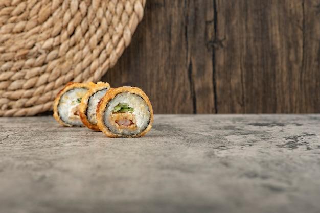 Conjunto de rolinhos quentes de sushi à milanesa na mesa de pedra