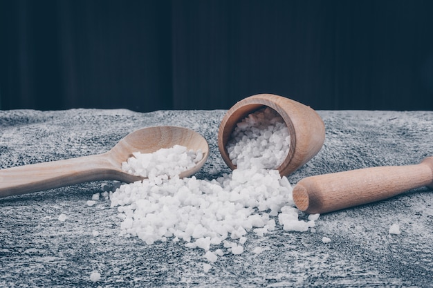 Conjunto de rolo e sal marinho em uma tigela e colher