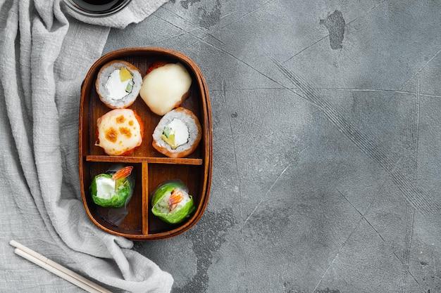 Conjunto de rolos de sushi bento, em fundo de pedra cinza, vista de cima plana, com copyspace e espaço para texto