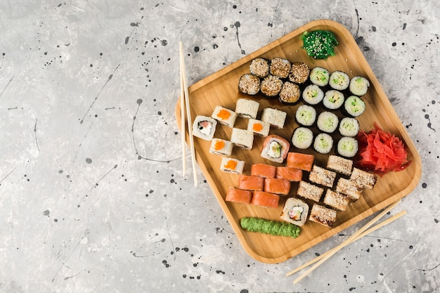 Conjunto de rolos de sushi com pauzinhos, wasabi e gengibre na mesa de madeira