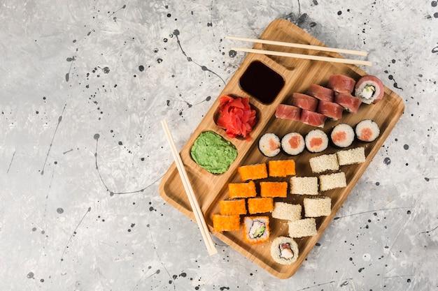 Conjunto de rolos de sushi com pauzinhos, wasabi e gengibre