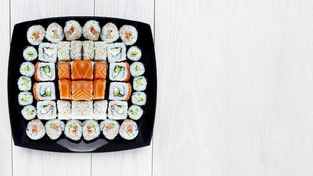 Conjunto de rolos de sushi de vários níveis de rolos diferentes em uma placa preta. fundo de madeira claro. lugar para texto. foco suave. conceito de sushi japonês.