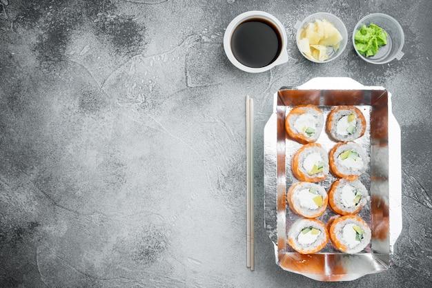 Conjunto de rolos de sushi em caixa de entrega de comida, em pedra cinza