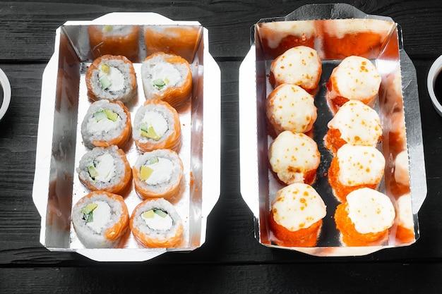 Conjunto de rolos de sushi em caixa de entrega de comida, mesa de madeira preta