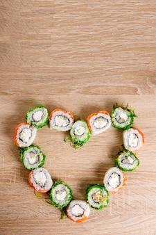 Conjunto de rolos de sushi em forma de coração para o dia dos namorados. conceito de menu ou entrega com espaço para texto. vista do topo.