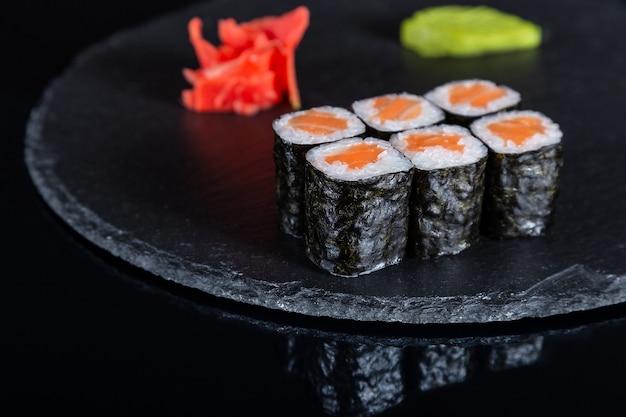 Conjunto de rolos de sushi em fundo preto